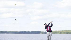 Golfari Peter Puhakka lyömässä palloa tiiauspaikalla.