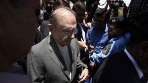 Zardari saapuu oikeustalolle kuvaajien ja poliisien ympäröimänä.