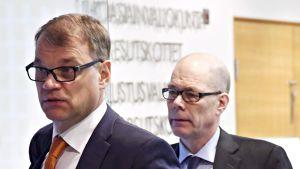 Kare Halonen kävelee Juha Sipilän takana Pikkuparlamentin käytävällä.