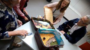 Matkalaukkuun tehty taideteos, jota taiteilija esittelee ikäihmisille.