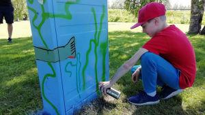 Nuori maalaa sähkökaappiin kaloja.