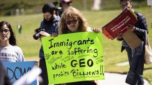Mielenosoitus. Kuvan keskellä olevalla naisella on kädessään kyltti, jossa sanotaan siirtolaisten kärsivän kun taas GEO saa miljardien voitot.