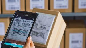 Viivakoodia skannataan postipaketin kyljestä älylaitteella.