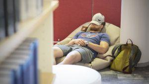 Opiskelija lepää kirjastossa.
