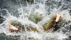 Poika hyppäsi veteen selällään vain jalkapohjat näkyvät pärskeiden seasta.