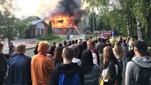 Tuppuralan koulu palaa Mikkelissä. Paloa on seuraamassa runsaasti yleisöä. Monet kuvaavat sammutustöitä.