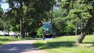 Ruohonleikkuukone ajamassa nurmea Isossapuistossa.