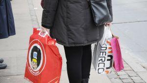 Nainen kantaa muovikasseissa ostoksia.