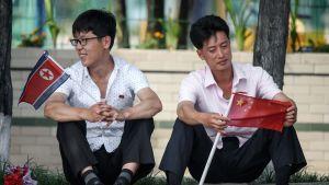 Kaksi miestä istuu Pohjois-Korea ja Kiinan liput käsissään Pjongjangissa.