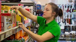 Kauppias järjestelee tuotteita päivittäitavarakaupan hyllylle