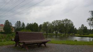 Maisema Tiklaslammen edestä, jossa puinen penkki