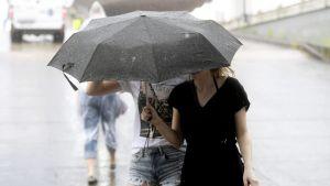 Ihmisiä sateenvarjon alla.