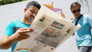 Iranilainen mies tutkii päivän uutisia sanomalehdestä Teheranissa.