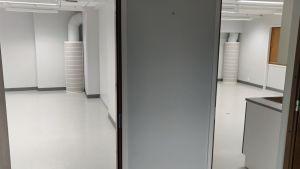 Kuvassa kaksi tyhjillään olevaa luokkaa koulurakennuksessa.