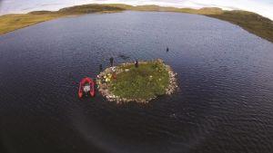 Pieni pyöreä saari, jolla ja jonka rantavedessä seisoo ihmisiä. Rannassa on myös kumivene.