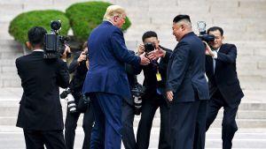 Donald Trump ja Kim Jong-un juuri kättelemässä.
