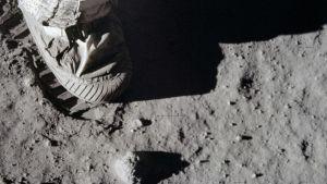 Astronautin jalka painamassa jälkeä Kuun pölyiseen pintaan.