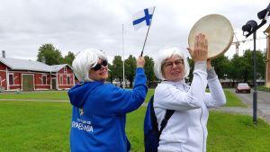 Joensuulaiset Liisa Joenperä (vas.) ja Sinikka Piirainen seisovat nurmikolla valkoiset peruukit päässä.