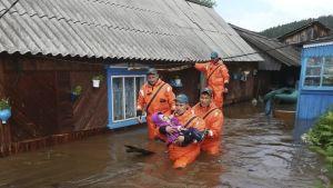 Pelastusmiehet kantavat pientä lasta tulvan keskellä.