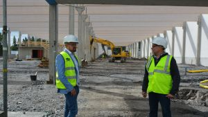 Kaksi miestä seisoo liivit päällä rakennustyömaalla