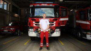 Palomies-ensihoitaja Sami Ruokolainen seisoo paloauton edessä Nurmeksen paloaseman kalustohallissa.