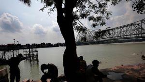 Ihmisiä vilvoittemassa puun alla Ganges-joen rannalla Kolkatassa, Itä-Intiassa.