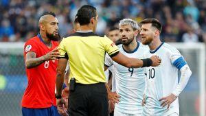 Chilen Arturo Vidal (vas.) ja Argentiinan Lionel Messi tuomaripuhuttelussa.