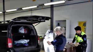Tullin työntekijät tarkistavat autoa Nuijamaalla.