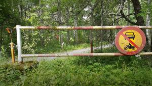 Vanha puomi ja liikennemerkki metsässä