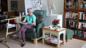 Kaisa Kotila lukee lehteä asunnossaan Ranuan Pappilannimessä.
