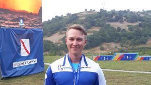 Timi Vallioniemi poseeraa mitali kaulassa.