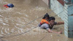 Mies kantoi tytärtään turvaan tulvaveden saartamassa Katmandussa.