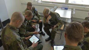 Varusmiehet selaavat tabletteja tuvassa.