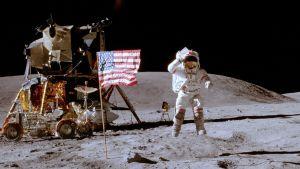 Astronautin takana lipputanko lippuineen sekä astronauttien kuukärry.