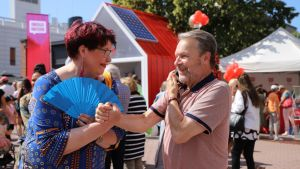 Ilkka Kanerva kättelee naista, jolla on käsissään sininen viuhka