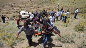 Tieltä suistunut bussi, pelastusmiehiä ja loukkaantuneita.