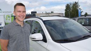 Toni Stenström ladattavan hybridin vieressä.