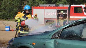 Kaksi palokuntanuorta harjoittelee autopalon sammuttamista.
