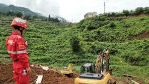 Avustustyöntekijä seisoo maanvyöryn keskellä Kiinassa
