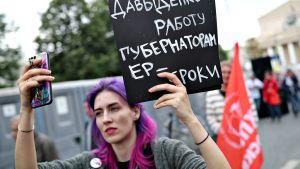 Moskovassa järjestettiin mielenosoitus ihmisoikeuksien puolesta 13. heinäkuuta 2019. Hiuksensa violetiksi värjännyt nainen pitelee vasemmassa kädessään kylttiä. Oikeassa kädessään hän pitelee älykännykkää ja ilmeisesti ottaa selfietä.