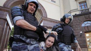 Poliisit raahaavat naista.