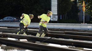 Miehet rakentavat Tampereella raitiotietä.