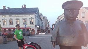 mies työntää lastenrattaita Oulun torilla