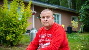 Kiuruvesiläinen Jari Nykkänen istuu talonsa edessä.