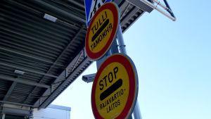 Tullin ja rajavartiolaitoksen liikennemerkit rajapuomilla.