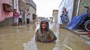 Vanha nainen seisoo tulvaveden valtaamalla kadulla kainaloita myöten monsuuni-sateiden aikana Karachissa, Pakistanissa.