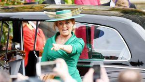 Sarah Ferguson näyttävässä hatussa osoittaa sormellaan kameroita.