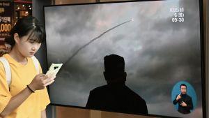 Eteläkorealaisella juna-asemalla näytetään uutislähetystä Pohjois-Korean ohjuskokeesta.
