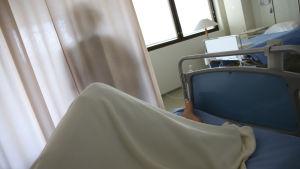 Potilas makaa potilashuoneen sängyllä.