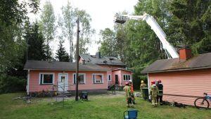 Pelastuslaitos seisoo asuinrakennuksen pihalla, koura-auto sammutti talon katon.